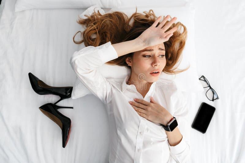 Nierada młoda biznesowa kobieta ubierał w formalnej odzieżowej koszula indoors kłama na łóżkowych pobliskich butach i telefonie obraz royalty free
