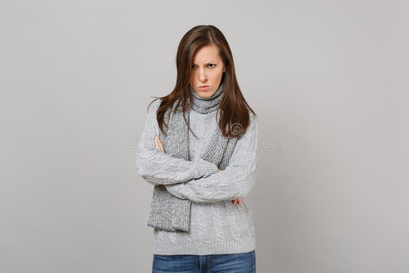 Nierada obrażająca młoda kobieta w szarym pulowerze, szalika chwyta ręki krzyżować na popielatym ściennym tle Zdrowy obrazy royalty free