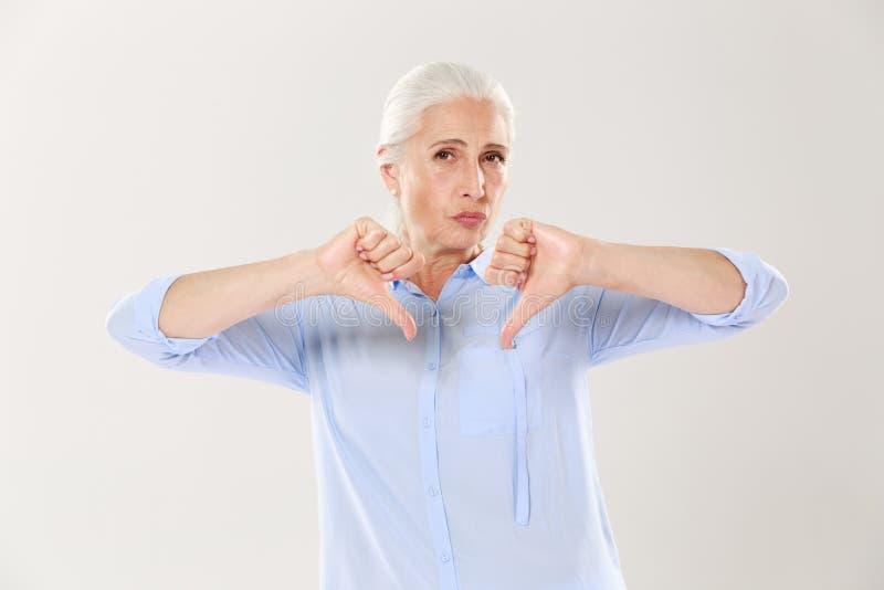 Nierada poważna stara kobieta pokazuje kciuka puszek i patrzeje t obraz stock
