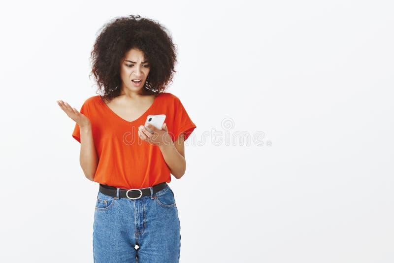 Nierada sfrustowana i szokująca atrakcyjna ciemnoskóra kobieta z afro fryzurą, gestykuluje nastroszonej palmy i patrzeć zdjęcia stock
