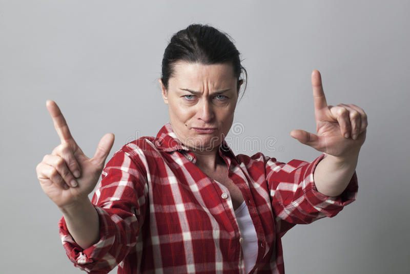 Nierada w średnim wieku kobieta pokazuje agresywnego ręka gest zdjęcie royalty free