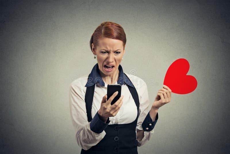 Nieradej młodej kobiety czytelnicza wiadomość na mądrze telefonie rzuca oddalonego czerwonego serce obraz royalty free