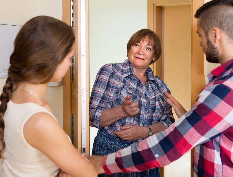 Nieradzi sąsiad dyskutuje w drzwi zdjęcia royalty free