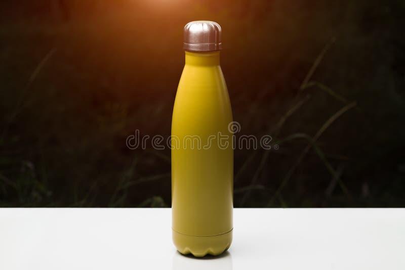 Nierdzewna thermo butelka dla wody, herbaty i coffe, na bielu stole Ciemny trawy tło z światło słoneczne skutkiem Termosu żółty k zdjęcie stock