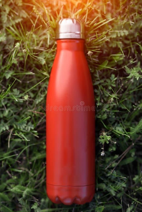 Nierdzewny butelka termos, czerwony kolor Na zielonej trawy tle obrazy royalty free