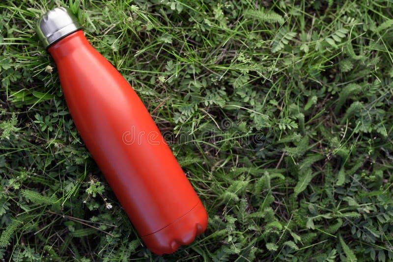 Nierdzewny butelka termos, czerwony kolor Na zielonej trawy tle zdjęcie royalty free