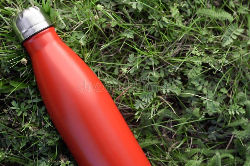Nierdzewny butelka termos, czerwony kolor Na zielonej trawy tle obrazy stock