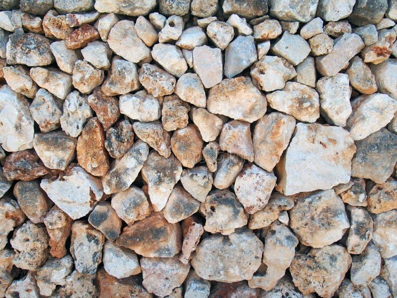 Nieregularna luźna kamienna ściana robić ampuła textured brąz i bielu wapień kołysa z starymi gałązkami przetykać w powierzchni zdjęcie royalty free