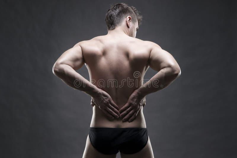 Nierenschmerz Mann mit Rückenschmerzen Hübscher muskulöser Bodybuilder, der auf grauem Hintergrund aufwirft Zurückhaltender Absch lizenzfreies stockfoto