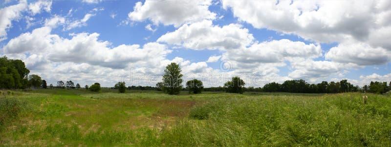 Nierozwinięty teren przemysłowy pod niebieskim niebem pełno białe puszyste cumulus chmury obraz royalty free