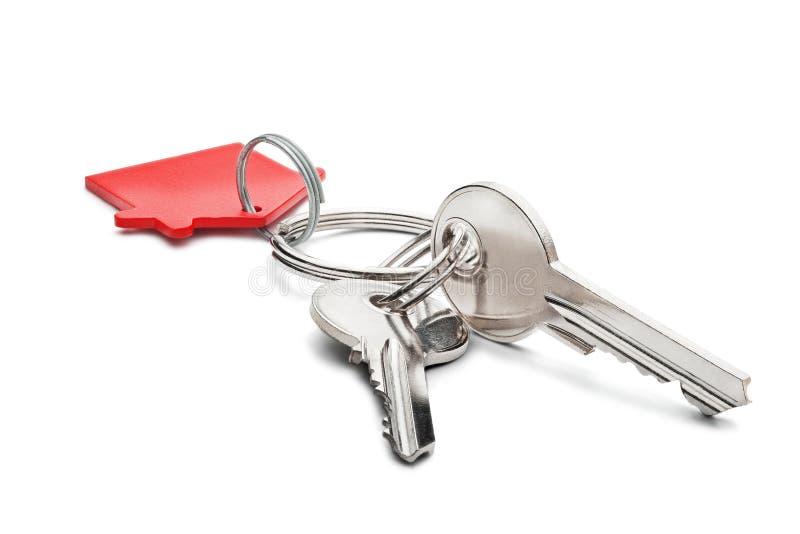 Nieruchomości pojęcie, czerwony kluczowy pierścionek i klucze na odosobnionym tle, obrazy royalty free