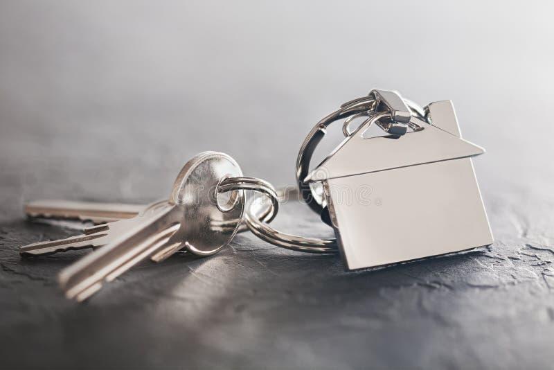 Nieruchomości pojęcie z kluczem, keychain z domowym symbolem, kamienny tło zdjęcie stock