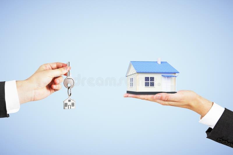 Nieruchomości pojęcie z mężczyzna ręką z kluczem i domem w inny zdjęcia stock