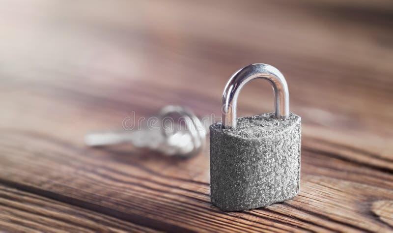 Nieruchomości pojęcie z symbolem ochrona, kędziorek kłódka z kluczem na drewnianym tle obrazy royalty free
