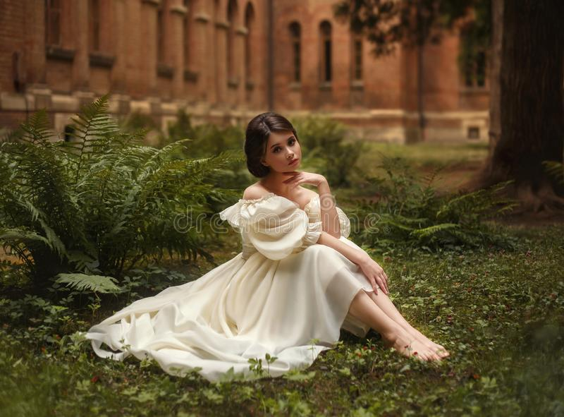 Niesamowicie piękny princess siedzi w grodowym ogródzie wśród mech i paproci Pięknie dziecięca twarz i zdjęcie royalty free