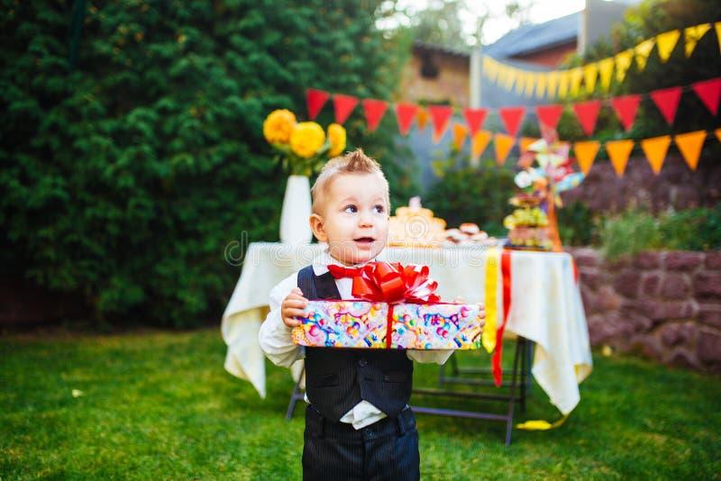 Niespodzianka dla urodziny chłopiec trzyma pudełko z prezentem w jardzie na tle świąteczny stół z a fotografia stock
