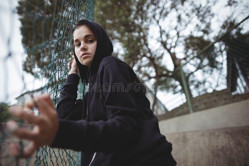 Niespokojna nastoletnia dziewczyna opiera na drucianej siatki ogrodzeniu przy szkolnym kampusem fotografia stock