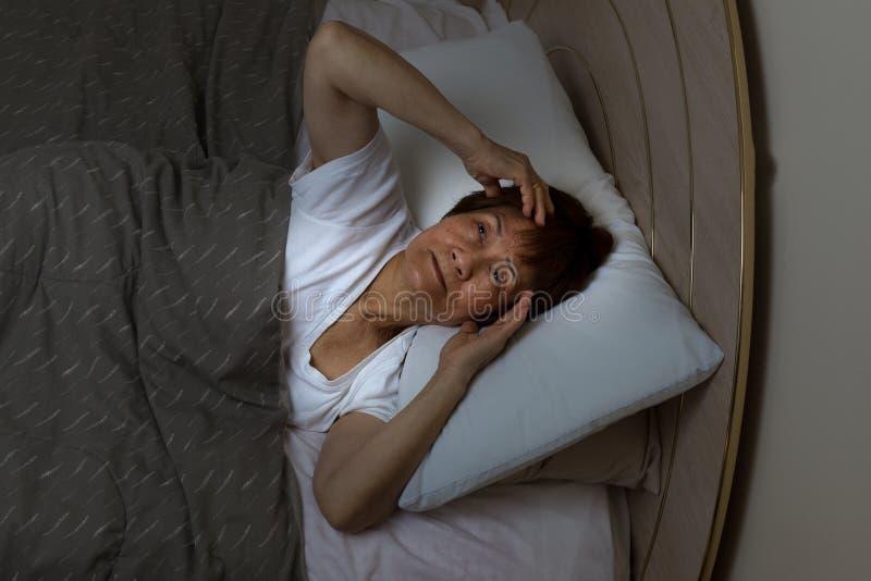Niespokojna starsza kobieta gapi się przy sufitem podczas nighttime podczas gdy fotografia royalty free