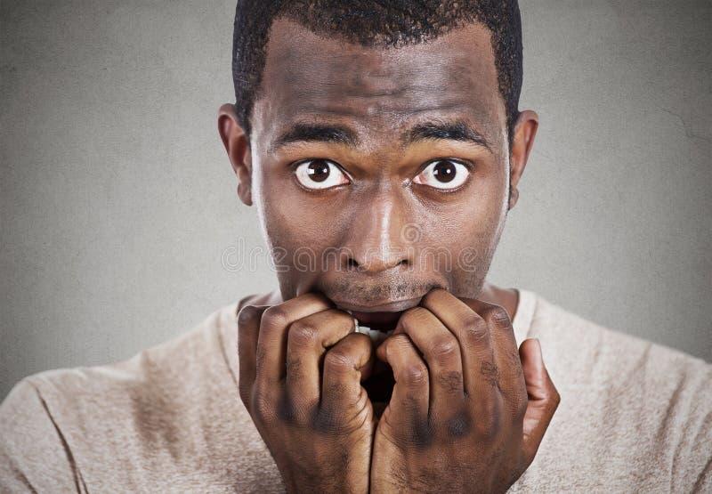 Niespokojnego mężczyzna zjadliwi paznokcie patrzeje ciebie kamera zdjęcia stock