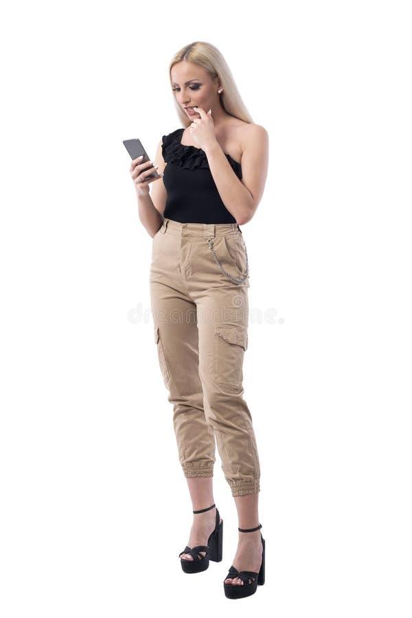 Niespokojnej nerwowej młodej blondynki kobiety gryzienia piękni gwoździe podczas gdy używać telefon komórkowego zdjęcie royalty free