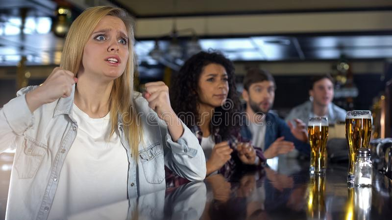 Niespokojny atrakcyjny blondynki dopatrywanie bawi się z przyjaciółmi w pubie, wspiera drużyny obraz stock