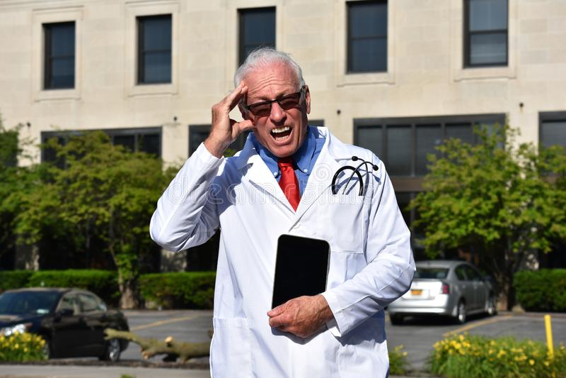Niespokojny Przystojny Starszy Męski chirurg Z pastylką Przy szpitalem obraz royalty free