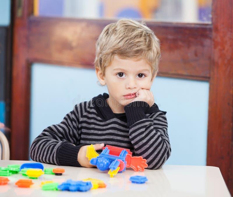 Nieszczęśliwa chłopiec Z blokami W sala lekcyjnej zdjęcia stock