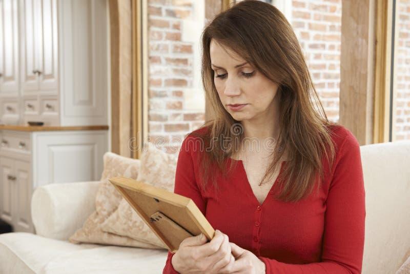 Nieszczęśliwa Dojrzała kobieta Patrzeje fotografię W ramie obraz royalty free