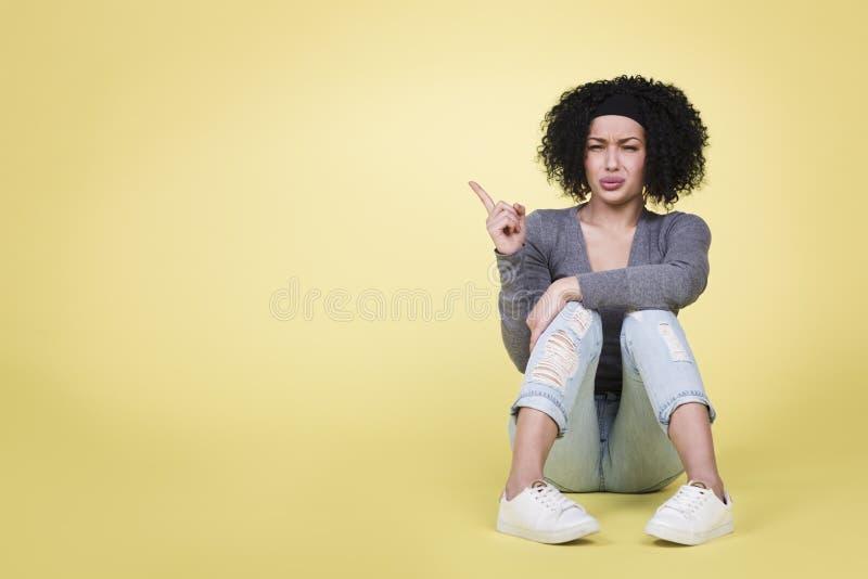 Nieszczęśliwa dziewczyna wskazuje up przy kopii przestrzenią obraz stock