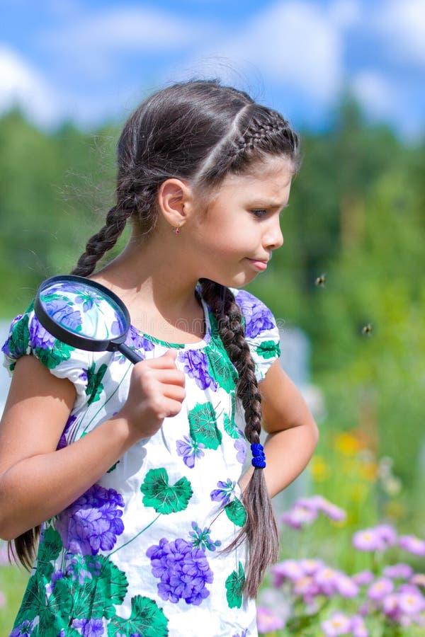 Nieszczęśliwa dziewczyna z powiększać - szkło w lecie obrazy stock