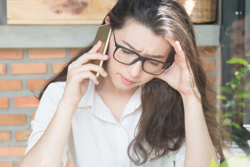 Nieszczęśliwa młoda kobieta używa jej mądrze telefon m?ody biznesowy online marketingowy poj?cie fotografia stock