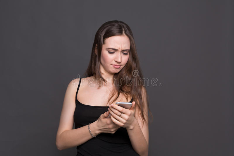 Nieszczęśliwa młoda kobieta używa smartphone portret zdjęcia stock