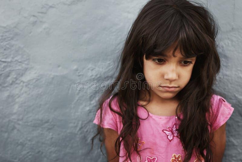 Nieszczęśliwa małej dziewczynki pozycja przeciw popielatej ścianie obraz royalty free