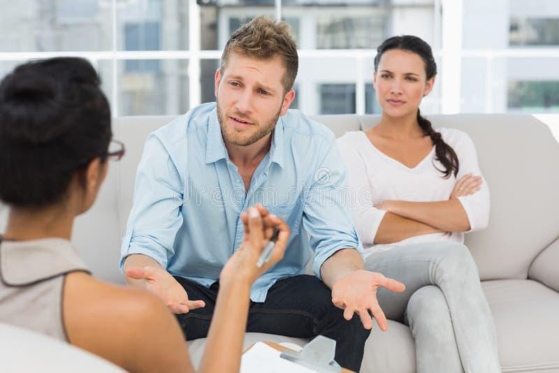 Nieszczęśliwa para przy terapii sesją z mężczyzna opowiada terapeuta obrazy royalty free