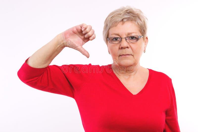 Nieszczęśliwa starsza kobieta pokazuje kciuki zestrzela, negatywne emocje w starości obraz royalty free