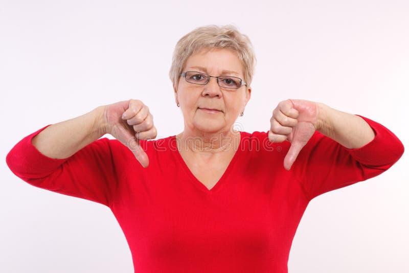 Nieszczęśliwa starsza kobieta pokazuje kciuki zestrzela, negatywne emocje w starości fotografia stock