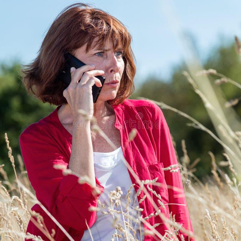 Nieszczęśliwa starzenie się kobieta opowiada na telefonie w długim trawy polu fotografia royalty free
