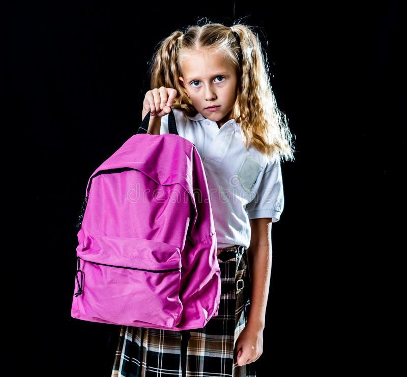Nieszczęśliwa szkolna dziewczyna trzyma dużego schoolbag książki i praca domowa odizolowywający na czarnym tle wewnątrz szkoła uc fotografia stock