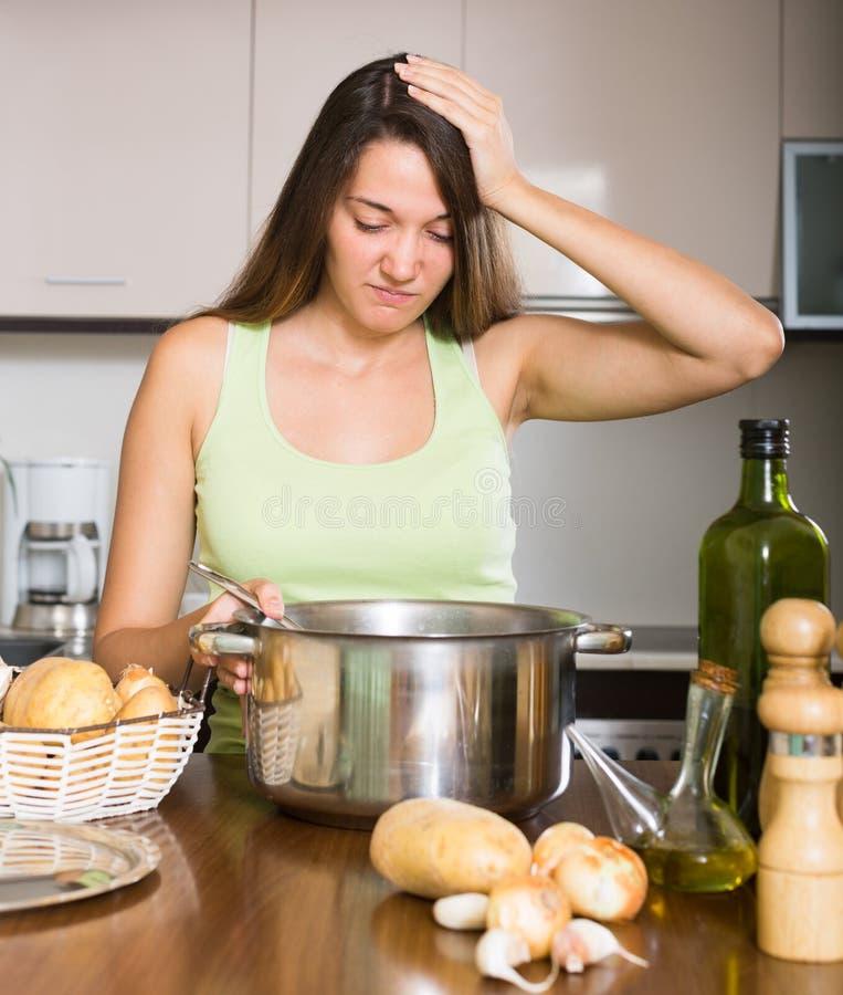 Nieszczęśliwego kobiety narządzania egzotyczny jedzenie z wybujałym zapachem zdjęcie stock