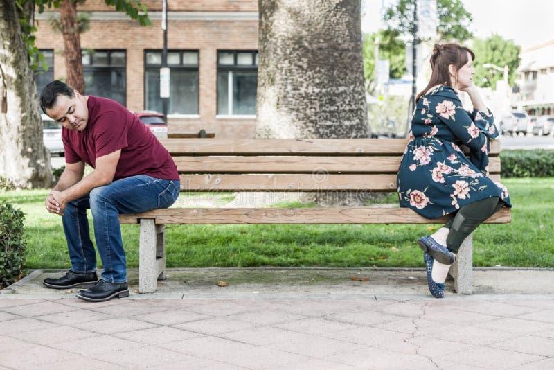 Nieszczęśliwej Mieszanej Biegowej pary Siedzący obszycie Zdala od Each Inny na Parkowej ławce obraz stock