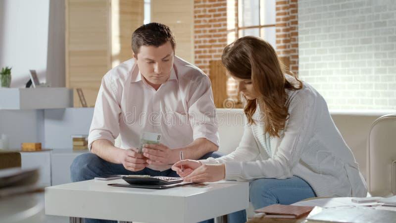 Nieszczęśliwej pary kalkulatorski dochód i koszty rodzinny budżet, bezrobocie obraz royalty free