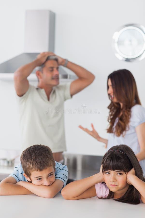 Nieszczęśliwi rodzeństwa siedzi w kuchni z ich rodzicami które są a obrazy stock