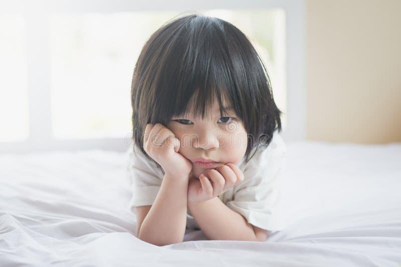 Nieszczęśliwy azjatykci dziecka lying on the beach na białym łóżku zdjęcie royalty free