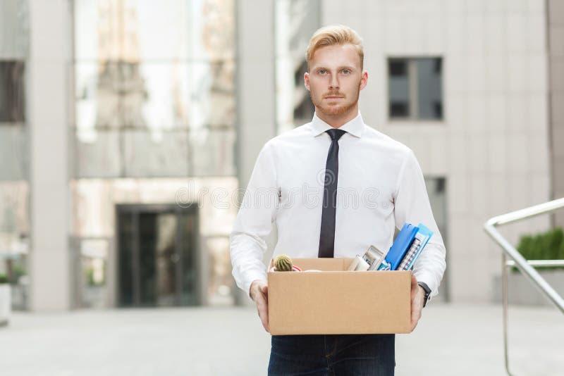 Nieszczęśliwy brodaty biznesowy mężczyzna iść out z kartonem, patrzejący kamerę i uczucie luźnych obraz royalty free