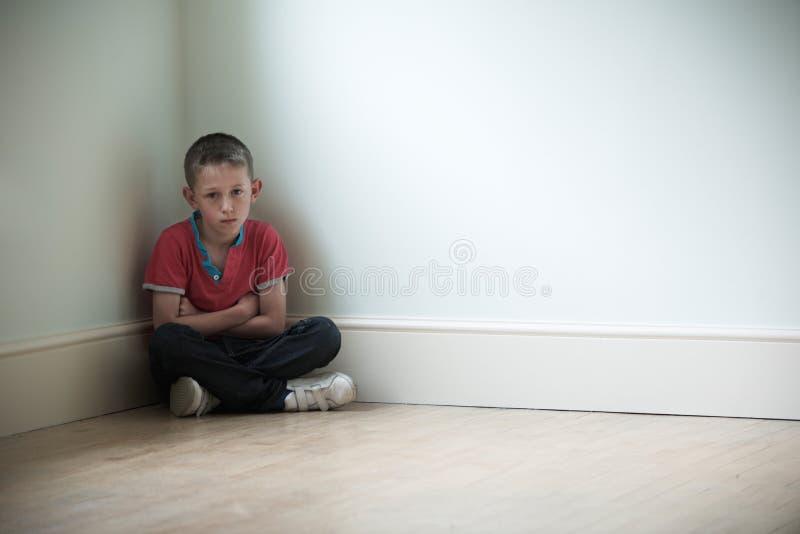 Nieszczęśliwy dziecka obsiadanie W kącie pokój obrazy stock