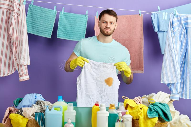Nieszczęśliwy mężczyzna robi sprzątaniu, trzyma brudny odziewa obraz royalty free