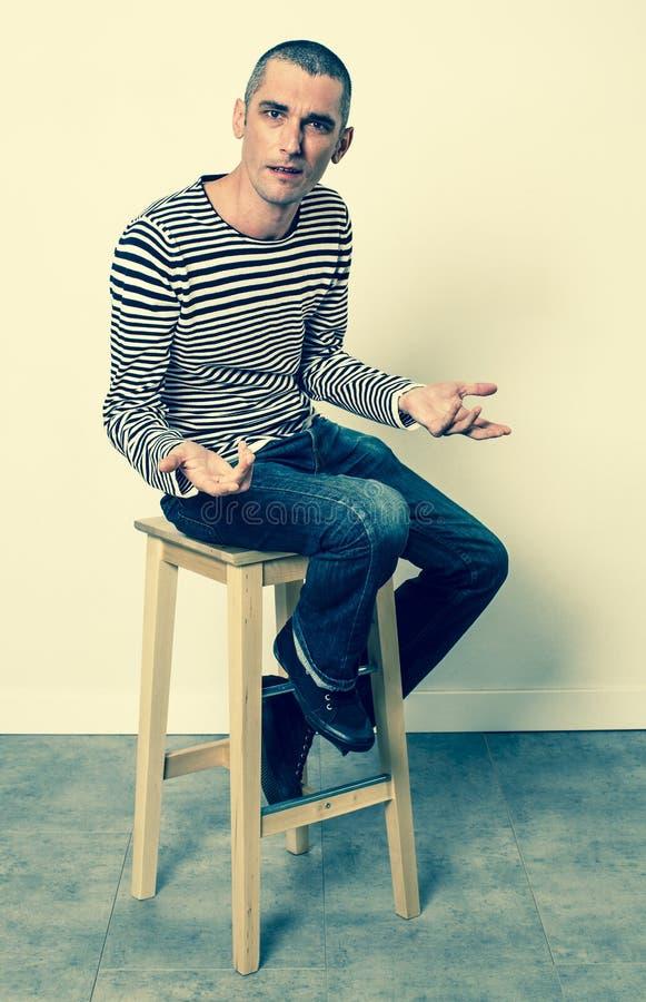 Nieszczęśliwy młody człowiek opowiada z rękami siedzi samotnie na stolec fotografia stock