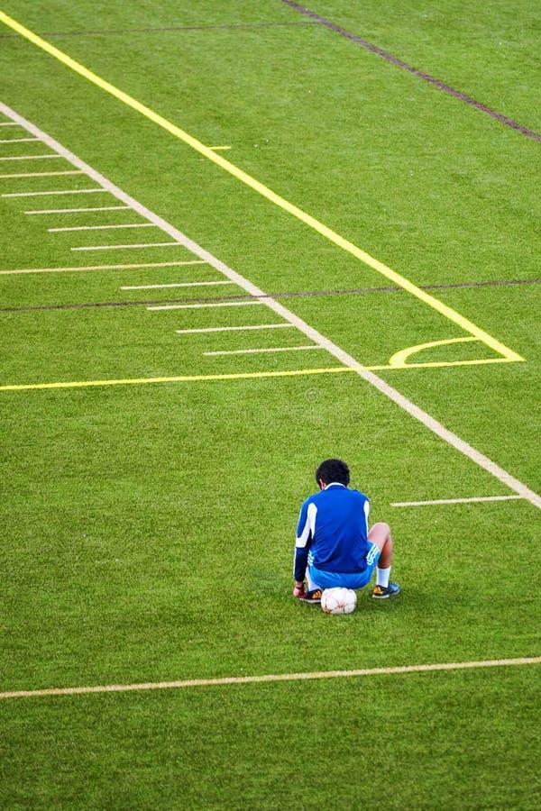 Nieszczęśliwy nastoletni chłopak wykluczający od piłki nożnej drużyny siedzi na piłce przy kątem zielony boisko piłkarskie obraz stock