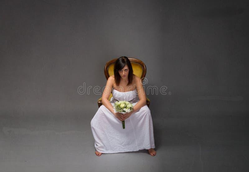 Nieszczęśliwy panny młodej obsiadanie z bukietem na ręce obrazy stock