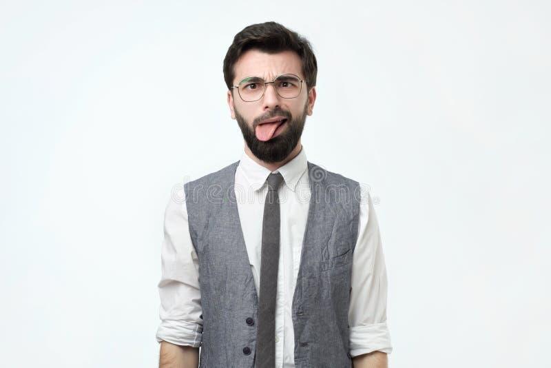 Nieszczęśliwy podrażniony brodaty młody człowiek jest ubranym białą koszula i kamizelka czuje nieradego, pokazuje jęzor zdjęcia royalty free